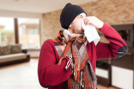 Sick man blowing his nose with paper handkerchief indoors with text area