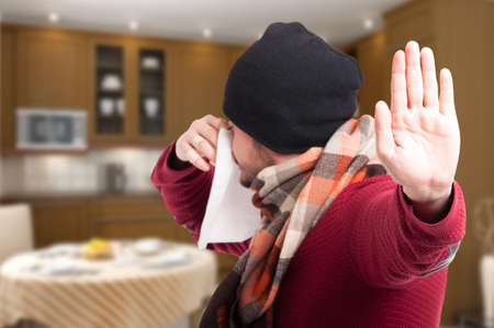 grippe: Male with fever and grippe doing stop gesture while blowing his nose into a napkin