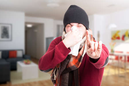 blowing nose: Young man with flu blowing his nose and showing wait gesture with finger