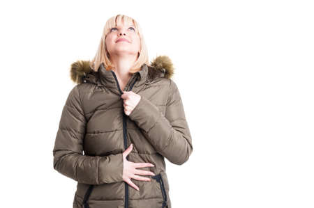 Pretty blonde girl zipping winter warm jacket and looking up isolated on white background with copy text space