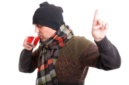 pointing herb: Sick man with flu drinking hot tea and doing waiting gesture on white background Stock Photo
