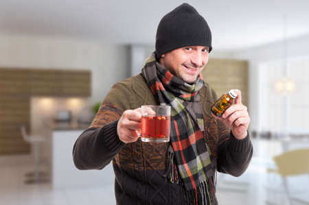 grippe: Attractive man holding hot tea and drugs as cold treatment concept