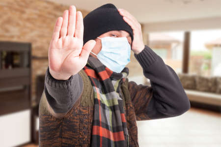 Sick man with protection mask against flu doing stop gesture with hand