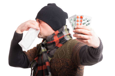 holding nose: Ill male blowing his nose into napkin and holding blister with pills isolated on white background