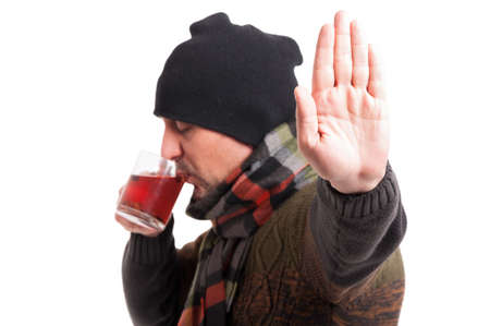 grippe: Male with influenza doing stop gesture while drinking a cup of tea isolated on white background Stock Photo