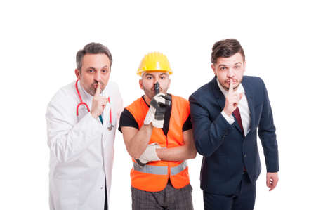 shush: Attractive medic, engineer and businessman doing quiet gesture on white studio background Stock Photo