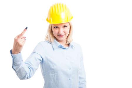 obscene: Female engineer wearing helmet showing obscene gesture isolated on white background