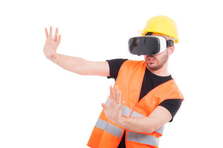 Male builder wearing futuristic vr glasses and doing rejection gesture isolated on white