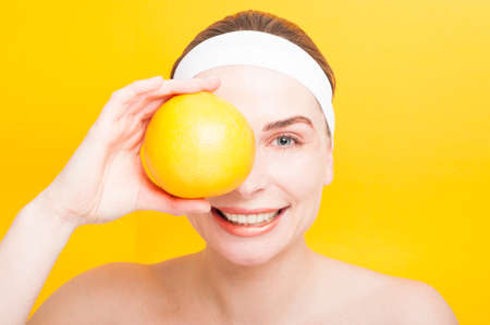 Portrait of woman holding big grapefruit in front of her eye isolated on yellow background
