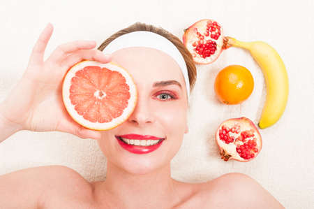Pure beauty model relaxing  with fresh face mask holding slice of grapefruit on eye Stock Photo