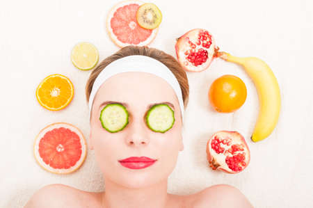 Fruit facial mask concept with young girl at dayspa relaxing with two slices of cucumber on eyes Stock Photo