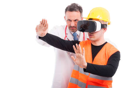 Medic helping constructor holding hands with virtual reality glasses isolated on white background with copy text space