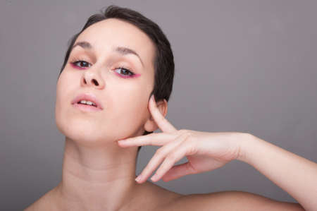 salud sexual: Beautiful woman face in close up touching her face on grey background Foto de archivo