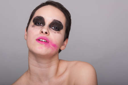 Woman face with smeared pink lipstick posing on grey studio background