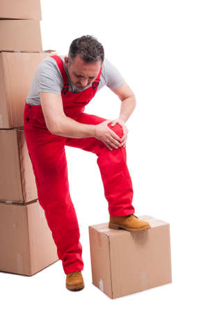 Full body of mover guy holding his knee like hurting with bunch of cardboard boxes around isolated on white background Stock Photo