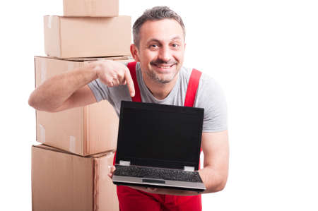 Mover guy holding and pointing blank screen laptop with cardboard boxes around isolated on white background