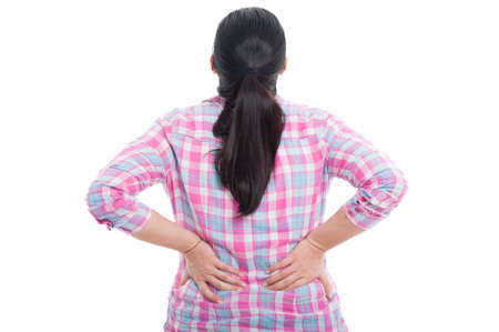Rear view of a female with lower back pain holding hands to her spine on white background