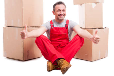Man sitting down surrounded by boxes showing like with both hands and smiling isolated on white background Stock Photo