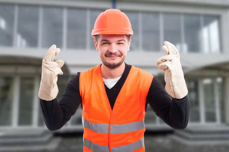 Cheerful architect with fingers crossed from both hands feeling lucky in front of building Stock Photo