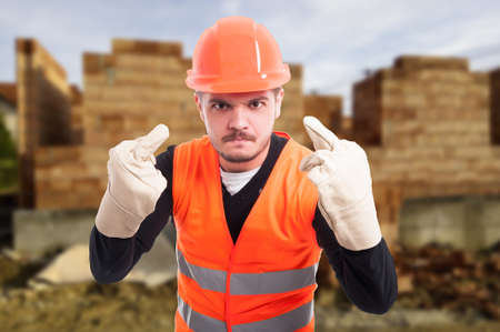 Angry or furious builder doing double offended gesture as arrogance and rudeness concept
