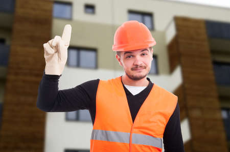 revelation: Cheerful builder pointing up his finger as new idea concept