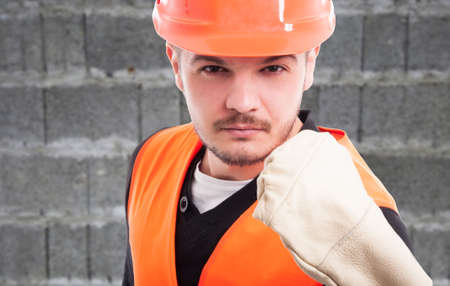 Portrait of violent constructor showing his fist in closeup view as work trouble concept Stock Photo