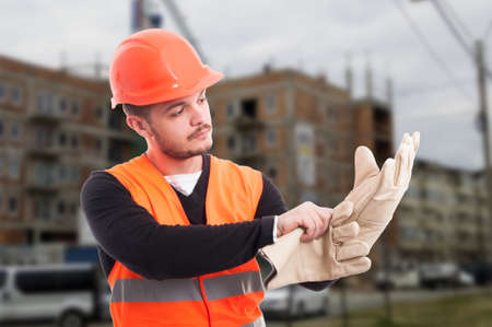 Builder putting protection gloves on hands and getting dressed for work