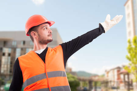 Low angle of construction worker showing or indicate something up outdoors