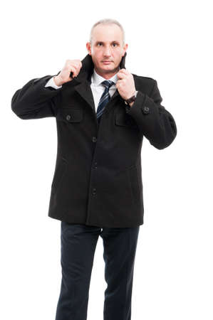 Middle age business man posing wearing elegant overcoat holding collar isolated on white background