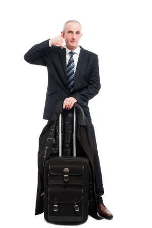 businessman waiting call: Middle age business man standing with carry on luggage showing calling gesture isolated on white background