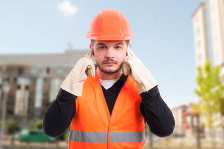 Male constructor doing hear no evil gesture by putting fingers in his ears to not hear a thing Stock Photo