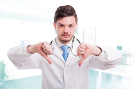 disapprove: Caucasian male doctor showing double thumb down sign or disapprove something