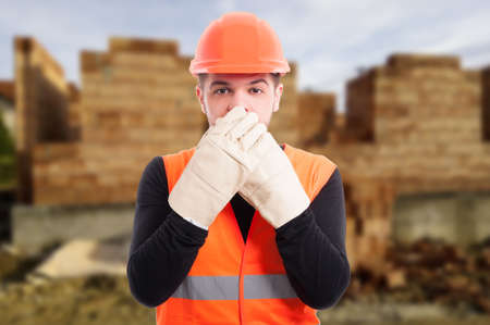 Male architect covering his mouth with hands doing speak no evil gesture