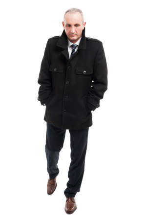 Full body of middle age business man walking with hands in pockets wearing overcoat isolated on white background