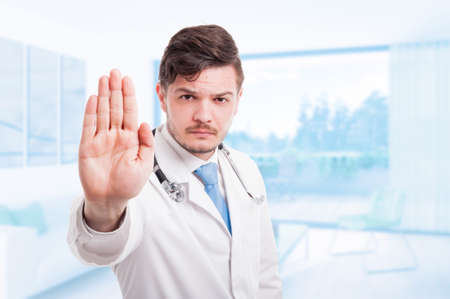 Angry male doctor in medical coat with repelling gesture with advertising area