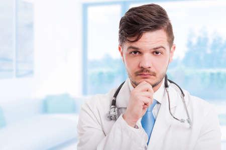 Portret van knappe peinzende arts in witte laag die hand op zijn kin houdt en met exemplaarruimte denkt