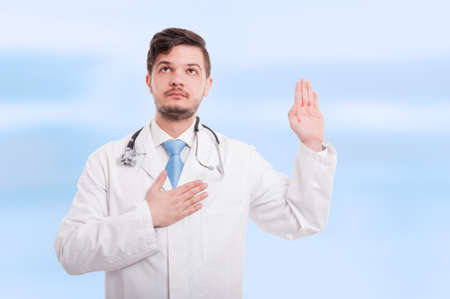 Confident doctor rising hand up doing loyalty gesture or making a oath on blue background