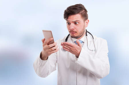 Young medic looking perplexed at his phone after seeing something interesting