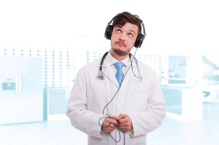 Male doctor with headphones listening music as medical relaxation concept