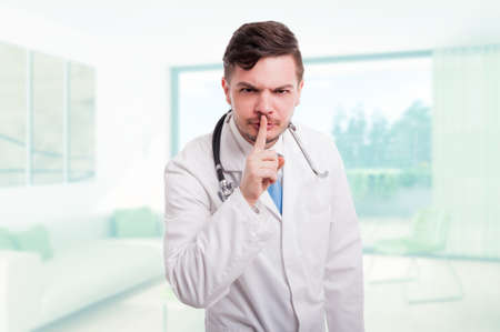 Serious male doctor indicate to keep silence or doing shush gesture in his office