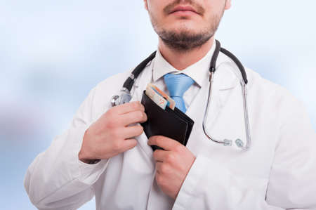 doctor putting money: Doctor putting money into his pocket in closeup view on blue background Stock Photo