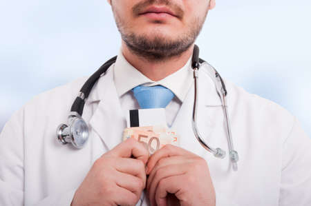 Close-up of medical doctor with money and debit card in hands as financial security concept