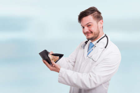 Happy yound doctor holding his wallet with euros as savings concept on blue background