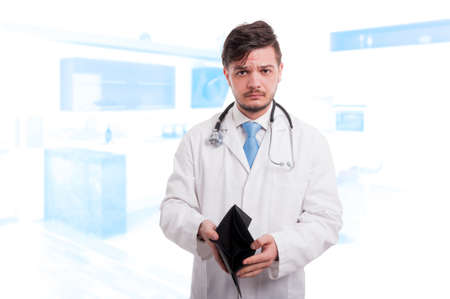 doctor money: Portrait of disspointed male doctor holding his empty wallet and having financial trouble