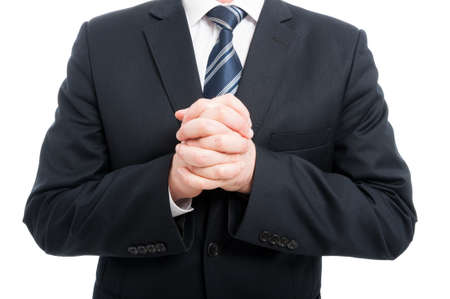 Close-up of elegant man holding his hands crossed wearing suit and tie isolated on white background