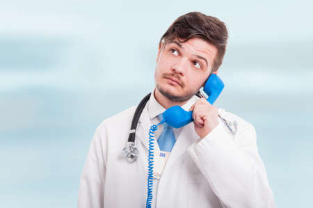 Male doctor talking on the phone and holding money in his coat on blue background