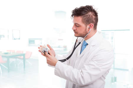 Young male doctor listening money with stethoscope as medical insurance concept