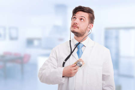 Handsome doctor holding money and listening heart with stethoscope Stock Photo