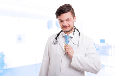doctor putting money: Handsome doctor putting money in his lab coat after payment from a patient Stock Photo