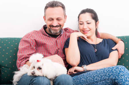 couple on couch: Portrait of happy couple holding puppy at home and spending great time together Stock Photo
